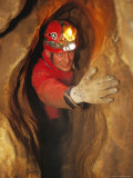 Man in Caving Gear in the Entrance to the Laundry Chute, a Narrow Corridor in the Rats Nest Cave Photographic Print by Mark Cosslett