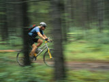 Panned View of a Cyclist Riding Along a Path Through Woods Photographic Print by Mark Cosslett