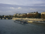 A Tourist Boat Cruises Along the Seine River Photographic Print by Charles Kogod