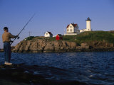A Fisherman Casts Towards the Historic Nubble Lighthouse at Twilight Photographic Print by Stephen St. John