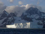 A Tabular Iceberg Floating Near a Mountainous Coastline Photographic Print by Ralph Lee Hopkins