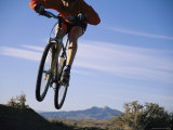 Cyclist Jumping with his Bicycle along a Wilderness Path Photographic Print