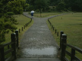 Pedestrian Walks down a Path in the Rain at the Imperial Palace Photographic Print