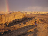 Woman Trail Running in a Rocky Landscape with a Rainbow Photographic Print by Bobby Model