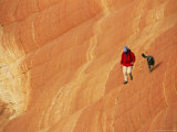 Man and his Dog Hiking on a Sandstone Rock Formation Photographic Print by Kate Thompson