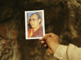 Monk Stretches Out his Hand Holding a Photo of the Dalai Lama Photographic Print