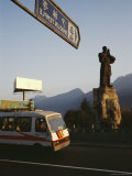Bus Passes by the Statue of Damo at the Entrance to Shaolin Photographic Print by Justin Guariglia