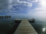 Lone Woman Sitting at End of a Pier near Over-Water Bungalows Photographic Print by Todd Gipstein