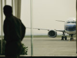 Man at a Chinese Airport Walks Past an Airplane Parked outside Lámina fotográfica por Justin Guariglia