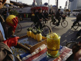 Cyclists Pass by a Street Vendor Selling Carved Pineapples Photographic Print