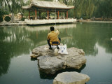 Man Fishes in a Green Pond Surrounded by Chinese Architecture Photographic Print