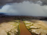 An Aerial View of a Coffee-Colored River with Rain in Distance Photographic Print by Randy Olson