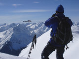 A Back-Country Skier Watches a Heli-Ski Chopper Approach a Peak Photographic Print by Skip Brown