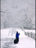 Woman Walks Along a Snowy Road with Skis and Luggage Photographic Print by Skip Brown