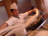 Chef Stretches Dough as He Makes Fresh Noodles in a Restaurant Photographic Print by Richard Nowitz