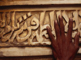 A Man Runs His Hand Over Arabic Script at the Famous Jama Masjid Photographic Print by Justin Guariglia