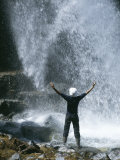 A Person Stands in the Spray of a Waterfall Photographic Print by John Dunn/Arctic Light