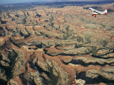 A Small Aircraft Hovers Above Above Canyonlands National Park Photographic Print by Joel Sartore