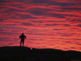 A Man Silhoutted against Red Twilight Sky Photographic Print