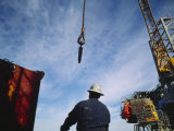 A Worker Uses a Crane and Hoist to Lift a Large Container onto an Oil Rig Photographic Print