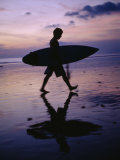 A Surfer Walks Along Kuta Beach at Dusk with His Surfboard in Hand Photographic Print