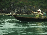 A Woman in a Traditional Boat Rows from Floating Village to Village, Halong Bay Photographic Print by Justin Guariglia