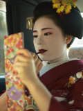 A Kimono-Clad Geisha Applies Lipstick in the Back of a Cab Lámina fotográfica