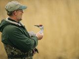 A Man Holds an Injured Sandhill Crane Photographic Print