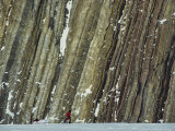 Skier Hauling Sled in Front of Steeply Dipping Sedimentary Strata Photographic Print by John Dunn/Arctic Light