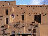 A Woman Climbs a Ladder to an Apartment in an Adobe Complex Photographic Print by Ira Block