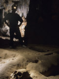 An Explorer Stands Over a Sacrificed Mayan Skull Embedded in the Cave Photographic Print