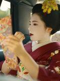 A Kimono-Clad Geisha Applies Lipstick in the Back of a Cab Photographic Print