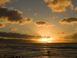 A Surfer Wades into the Water at Rocky Point at Sunset Photographic Print by Charles Kogod