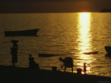 Silhouetted Malawian Women and Children on the Lake Shore at Twilight Photographic Print by Bill Curtsinger