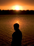 Silhouette of a Child against a Lake at Sunset Photographic Print by Raul Touzon