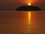 The Sun Casts a Red Glow and a Reflection as It Sets Behind an Island Photographic Print by Nicolas Reynard