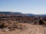 Dirt Road Leads Past Cliffs and Mesas Through a Desert Landscape, Capitol Reef National Park, Utah Photographic Print by Taylor S. Kennedy