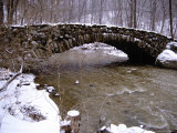 An Old Stone Bridge Over Rock Creek During a Snow Storm Photographic Print by Stephen St. John