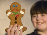 A Gingerbread Cookie Looks Sad While Being Held in a Male's Hand Photographic Print by Joel Sartore