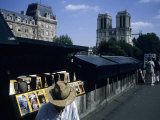 A Man Sells Magazines Along the Seine River with Notre Dame Visible, Paris, France Photographic Print by Taylor S. Kennedy