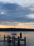 A Woman Stands on a Dock Looking at the Sunset Photographic Print by Taylor S. Kennedy