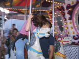 Young Couple Kissing on Carousel Photographic Print