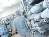 Doctor Walking Through Hospital Closet with Blue Sheets and Scrubs Photographic Print