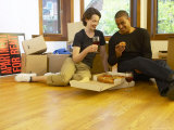 Couple Eating Pizza and Drinking Red Wine on Moving Day Photographie