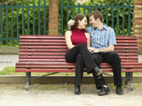 Smiling Couple Sitting on Park Bench Photographic Print