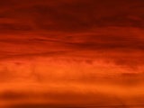 A Deep Red Sunset with Glowing Clouds and Dark Sky Photographic Print