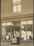 Woman Standing in the Doorway of a Modest Clothing Shop Photographic Print