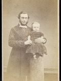 Man in a Frock Coat and Light Coloured Necktie Holds a Very Small Child on a Plinth Photographic Print