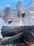 Shoes Drying on Sticks Next to Campfire Photographic Print by Donald Higgs