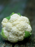 Close-up of Baby Cauliflowers on Rustic Table Photographic Print by James Guilliam